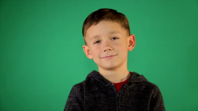 Portrait of a child on a green background Portrait of a cute boy on a green background one boy only stock videos & royalty-free footage