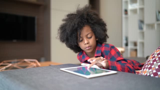 vídeos de stock e filmes b-roll de portrait of a child playing with digital tablet at home - afro