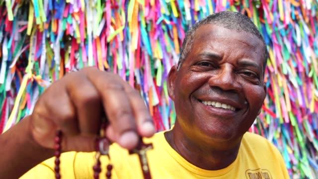 haçı gösterilen bir christian adam portresi - pazarcı stok videoları ve detay görüntü çekimi