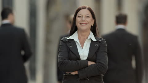 HD: Portrait Of A Confident Businesswoman HD1080p: Senior executive smiling and looking at the camera with confidence while standing outdoors on a city street with people walking in background. medium shot stock videos & royalty-free footage