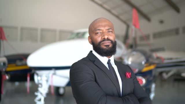 Portrait of a confident man looking at camera in a hangar Portrait of a confident man looking at camera in a hangar ceo stock videos & royalty-free footage