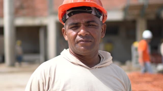 portrait of a construction worker in a construction site - латиноамериканская и испаноговорящая этнические группы стоковые видео и кадры b-roll