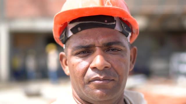 porträt eines bauarbeiters in einer baustelle - arbeiter stock-videos und b-roll-filmmaterial