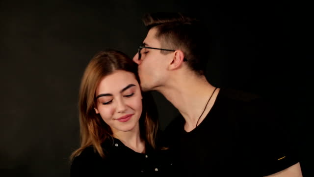 portrait of a couple in love on a black background - brunette woman eyeglasses kiss man video stock e b–roll