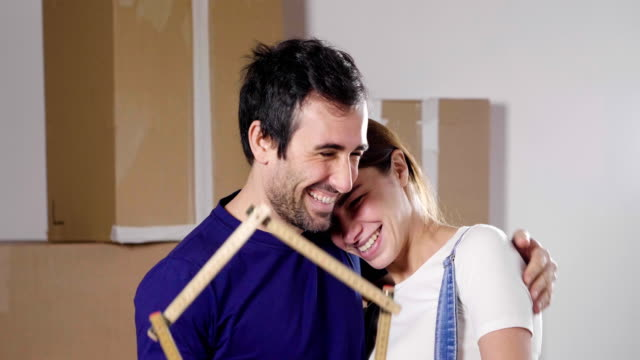 portrait of a couple in love who have just bought a house and is moving. the bride and groom smile and hold the house-shaped meter in their hands. - key ring stock videos & royalty-free footage