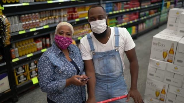 vídeos de stock e filmes b-roll de portrait of a couple with disposable medical mask shopping in supermarket - afro latino mask