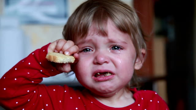 Portrait of a crying baby girl holding a dry bread video