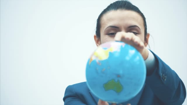 Portrait of a cute and happy female teacher on a white background. During this time, the globe holds on its elongated hands. Close-up.