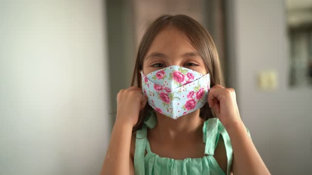 Portrait of a cute girl removing protective face mask at home video