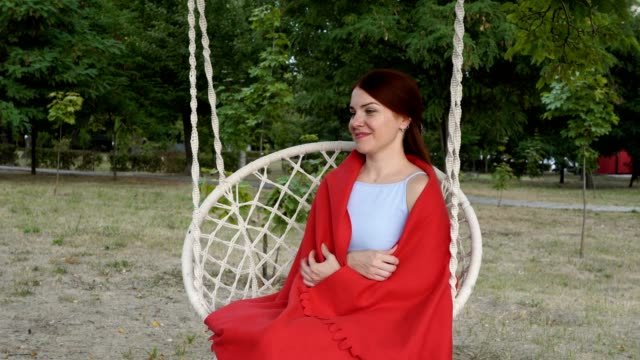 Portrait of a cute girl with red hair under a red plaid, who sits and poses on a swing in the park at the sunset of a summer day. She smiles and looks away. Close-up. 4K.