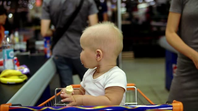 Portrait of a cute little baby eating banana and sitting in a shopping cart while her mother is taking out products from the cart and putting them on conveyor belt at the supermarket video