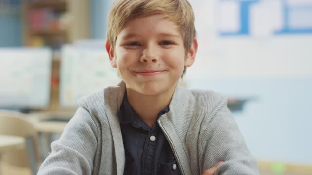 porträt eines niedlichen kleinen jungen sitzt an seinem schultisch, lacht glücklich. smart little boy mit charmantem lächeln sitzen im klassenzimmer. erhöhen kamera schuss. zeitlupe - grundschule stock-videos und b-roll-filmmaterial