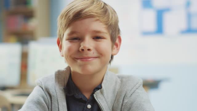 porträt eines niedlichen kleinen jungen sitzt an seinem schultisch, lächelt glücklich. smart little boy mit charmantem lächeln sitzen im klassenzimmer. nahaufnahme kameraaufnahme - grundschule stock-videos und b-roll-filmmaterial