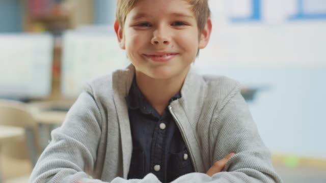 porträt eines niedlichen kleinen jungen sitzt an seinem schultisch, lächelt glücklich. smart little boy mit charmantem lächeln sitzen im klassenzimmer. erhöhen der kameraaufnahme - grundschule stock-videos und b-roll-filmmaterial