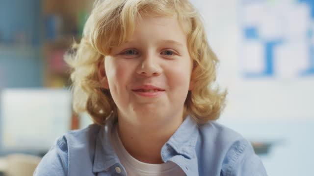 porträt eines niedlichen kleinen jungen mit lockigen blonden haaren sitzt an seinem schultisch, lächelt glücklich. smart little boy mit charmantem lächeln sitzen im klassenzimmer. nahaufnahme kameraaufnahme - grundschule stock-videos und b-roll-filmmaterial