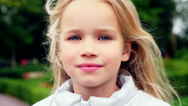 portrait of a cute little girl outdoors - capelli biondi video stock e b–roll