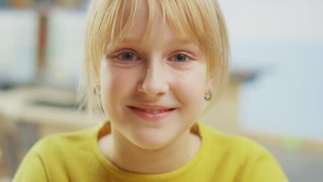 porträt eines niedlichen kleinen mädchens mit blonden haaren sitzt an ihrem schultisch, lächelt glücklich. smart little girl mit charmantem lächeln sitzen im klassenzimmer. nahaufnahme kameraaufnahme - grundschule stock-videos und b-roll-filmmaterial