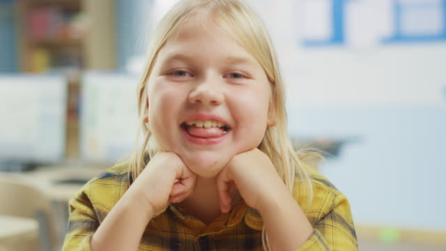 porträt eines niedlichen kleinen mädchens mit blonden haaren sitzt an ihrem schultisch, lächelt glücklich, zeigt zunge spöttisch. smart little girl mit lächeln sitzen im klassenzimmer. nahaufnahme kameraaufnahme - grundschule stock-videos und b-roll-filmmaterial