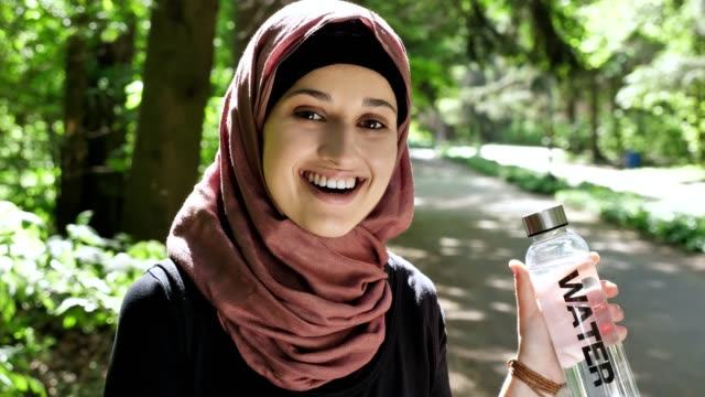 portrait of a cute young girl in a hijab with a bottle of water in her hands, smiling, looking at the camera, park in the background. 50 fps - abbigliamento modesto video stock e b–roll