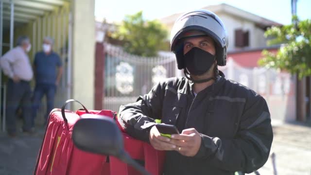 porträt eines liefermannes mit gesichtsmaske auf der straße - brasilianischer abstammung stock-videos und b-roll-filmmaterial
