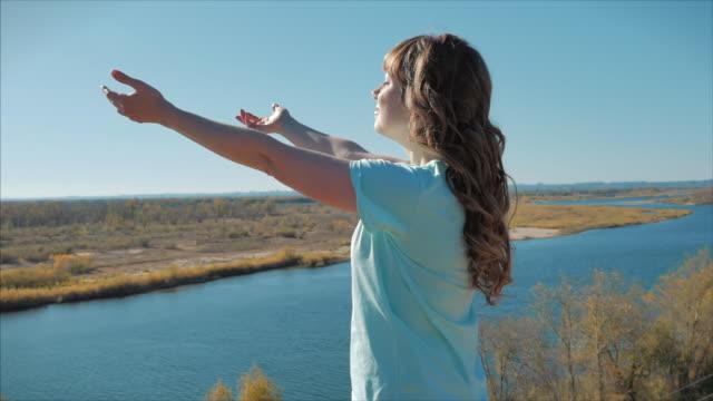 портрет европейской женщины или девушки, поднимая лицо к солнцу. женщина получает витамин d от солнца - vitamin d стоковые видео и кадры b-roll
