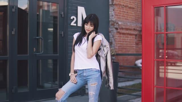 stockvideo's en b-roll-footage met portret van een modieus meisje op de achtergrond van de architectuur van de stad. mooie jonge vrouw in jeans en jas - dierenhuid huid