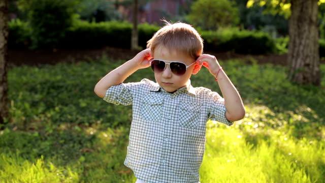portrait of a fashionable little boy in sunglasses in a park on green grass. - solo neonati maschi video stock e b–roll