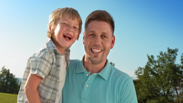 SLO MO Portrait of a father holding his son and smiling into the camera video