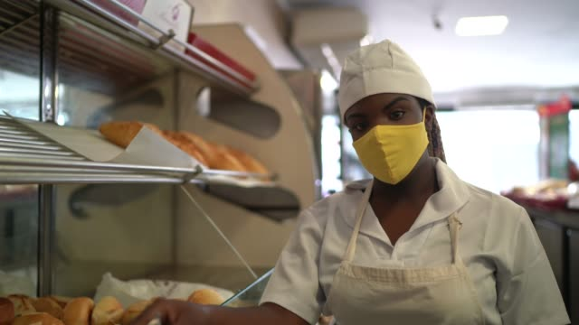 vídeos de stock e filmes b-roll de portrait of a female baker picking up bread with face mask - afro latino mask