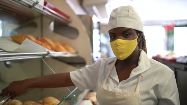 Portrait of a female baker picking up bread with face mask video