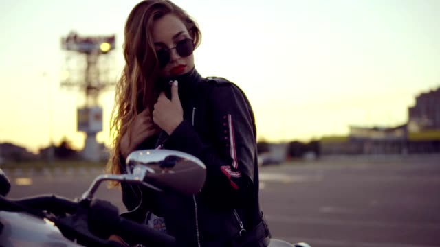 portrait of a female biker in leather jacket and shorts sitting on her bike and holding a handlebar. close up of young sexy curly woman in sunglasses on the chopper - giacca video stock e b–roll