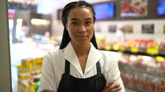 Portrait of a female butcher standing with arms crossed in front of a butchers shop