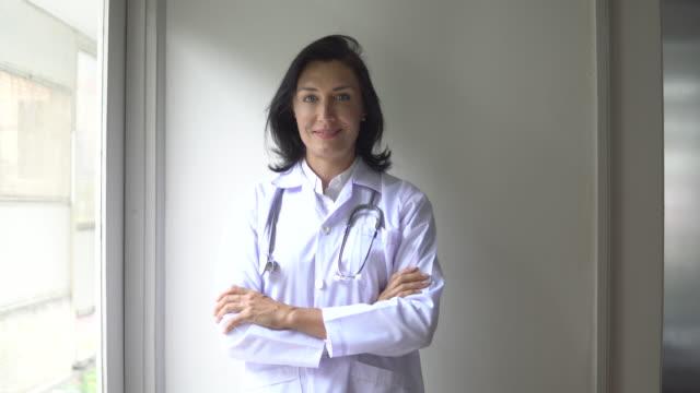 vidéos et rushes de verticale d'un docteur féminin dans une robe blanche restant dans son bureau - une seule femme d'âge mûr