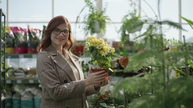 portrait of a female florist with glasses for vision choosing decorative blooming plants in pots for home or office design in a flower shop standing on a background of green plants, gardening - direttrice video stock e b–roll