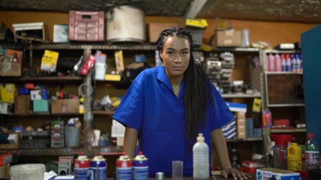 porträt einer mechanikerin, die in einer autowerkstatt hinter der theke steht - brasilianischer abstammung stock-videos und b-roll-filmmaterial