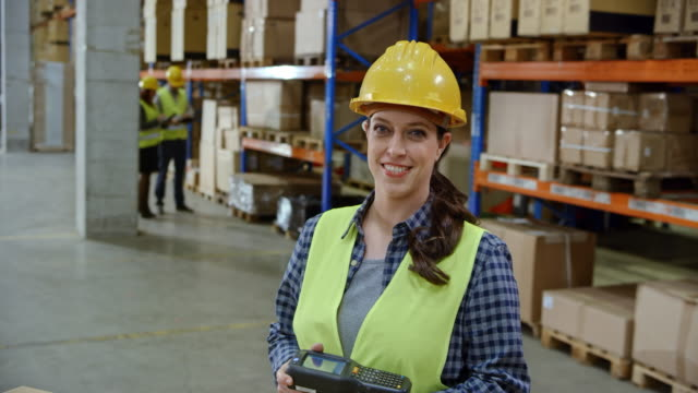 Portrait of a female warehouse employee with a handheld scanner in her hands video