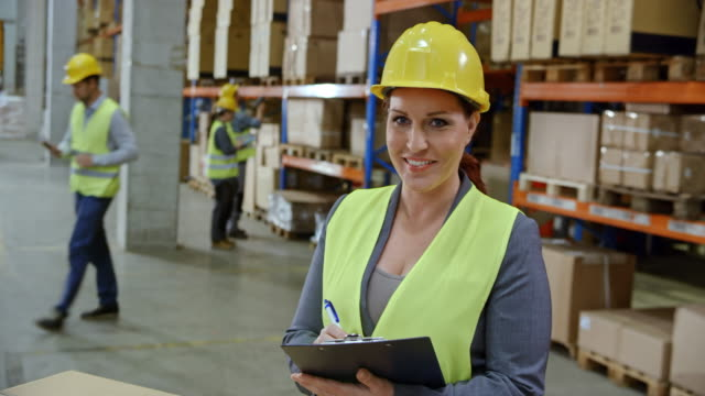 Portrait of a female warehouse supervisor Wide handheld shot of a female warehouse supervisor smiling into the camera standing by the pallet in the warehouse with a clipboard in her hands. Shot in Slovenia. happy boss stock videos & royalty-free footage