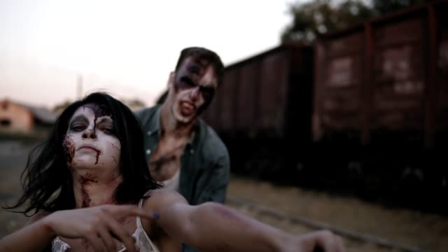 Portrait of a female zombie with wounded face in bloody dress shouting and zombie man behind her coming on . Abandoned town and railway wagons on the background Portrait of a female zombie with wounded face in bloody dress shouting and zombie man behind her coming on . Abandoned town and railway wagons on the background. vampire stock videos & royalty-free footage
