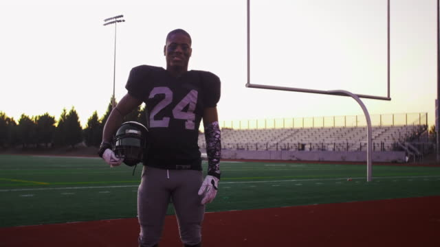 Portrait of a football player on a field holding his helmet and smiling video