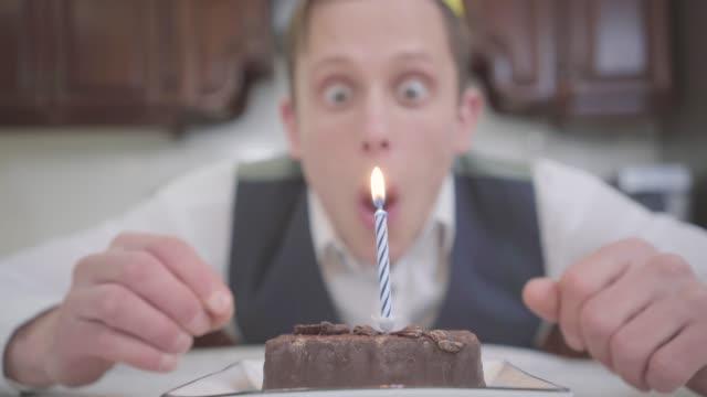 vidéos et rushes de verticale d'un jeune homme heureux drôle dans le chapeau d'anniversaire soufflant dehors la bougie - 20 24 ans