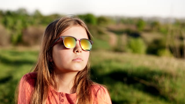 Portrait of a girl in sun glasses at sunset video