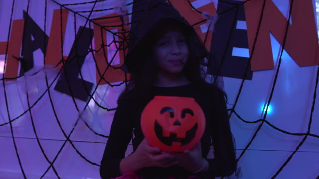 Portrait of a girl in witch costume holding orange pumpkin bucket