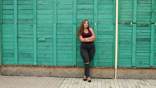 Portrait of a girl model plus size on the background of a green wall. Portrait of a girl model plus size on the background of a green wall. A young girl with a full figure walks in the Park in the summer against a green wooden wall. plus size model stock videos & royalty-free footage