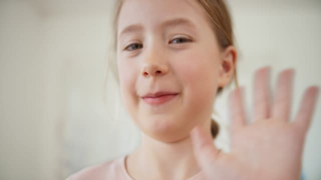SLO MO Portrait of a girl smiling into the camera and waving Slow motion medium handheld shot of a smiling girl waving into the camera. Shot in Slovenia. one girl only stock videos & royalty-free footage