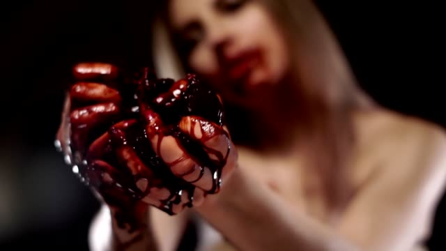 Portrait of a girl who breaks a bloody heart, stretched out in front of him, hands.