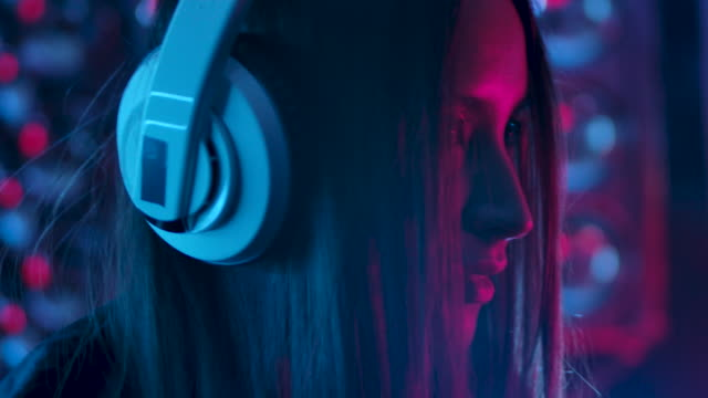 Portrait of a Girl Who Listening to Music in Earphones and Dancing Portrait 30s Girl Who Listening Music in Earphones mp3 Player and Dancing on Party Enjoy Evening in Slow Motion. Young Attractive Woman Looking at Camera Indoors with Colorful Purple Light CloseUp 4K east asian ethnicity stock videos & royalty-free footage