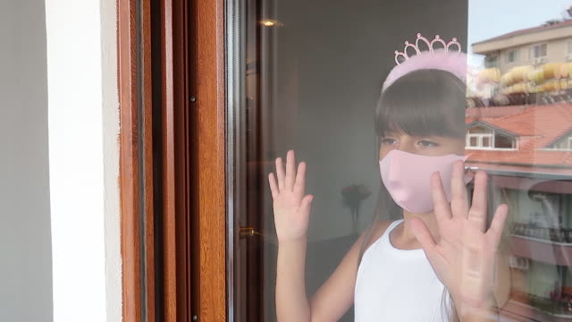 Portrait of a girl with a protective mask behind to window