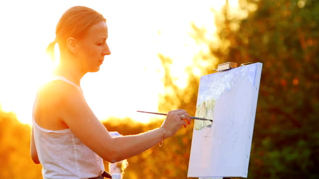 Portrait of a girl with white hair in a white t-shirt, depicting a landscape on canvas in sunset in the sun using oil paint and brush video