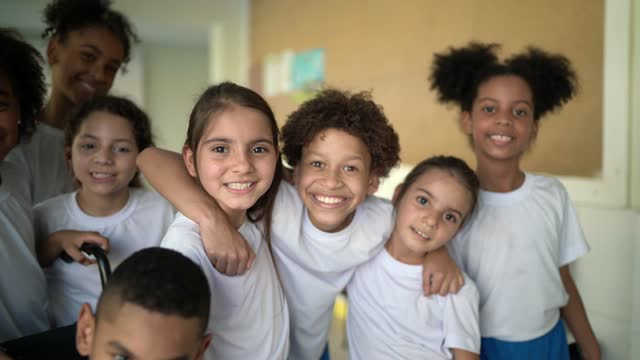 Portrait of a group of elementary students embracing video