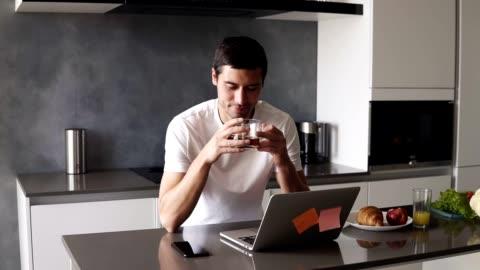 vídeos y material grabado en eventos de stock de retrato de un hombre caucásico relajado guapo con una camisa blanca sentado en la cocina frente a su ordenador portátil y teléfono inteligente. chico bebiendo un té negro de la taza transparente y sonriendo pacíficamente - gente tranquila